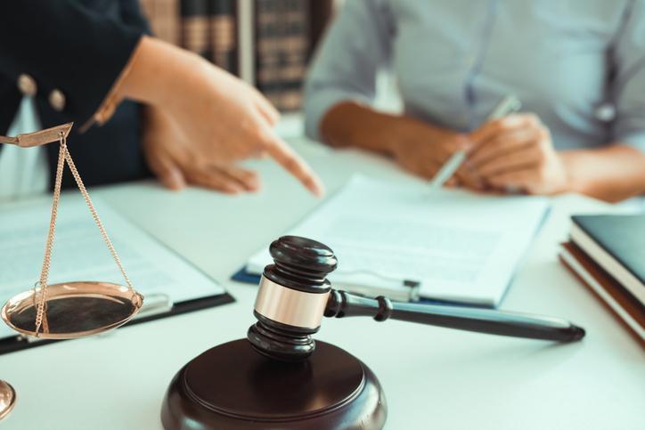 młotek sędziowski wtle dwie osoby sprawdzające dokumenty