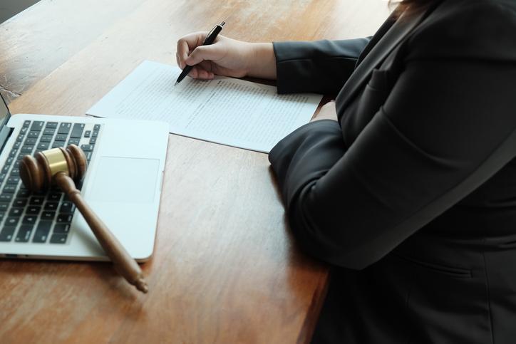 kobieta czytająca dokument obok niej stoi laptop ananim leży młotek sędziowski