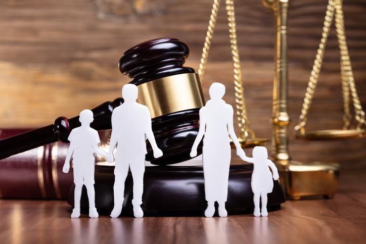postacie dorosłych idzieci stojące przed młotkiem sędziowski