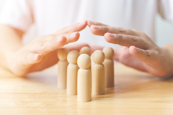 dłonie naddrewnianymi figurkami przypominającymi ludzi